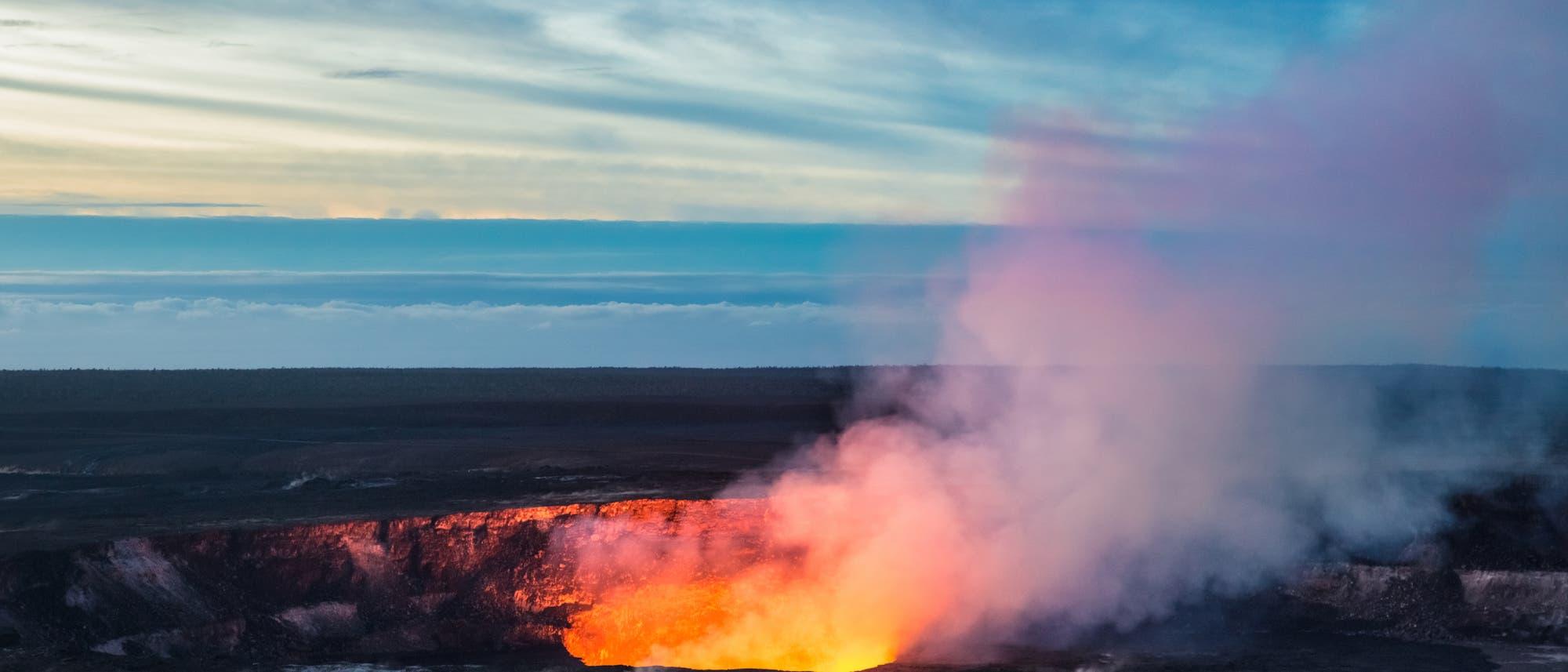 Blick auf den Gipfelkrater des Kilauea mit Lavasee, im Hintergrund Wolken.