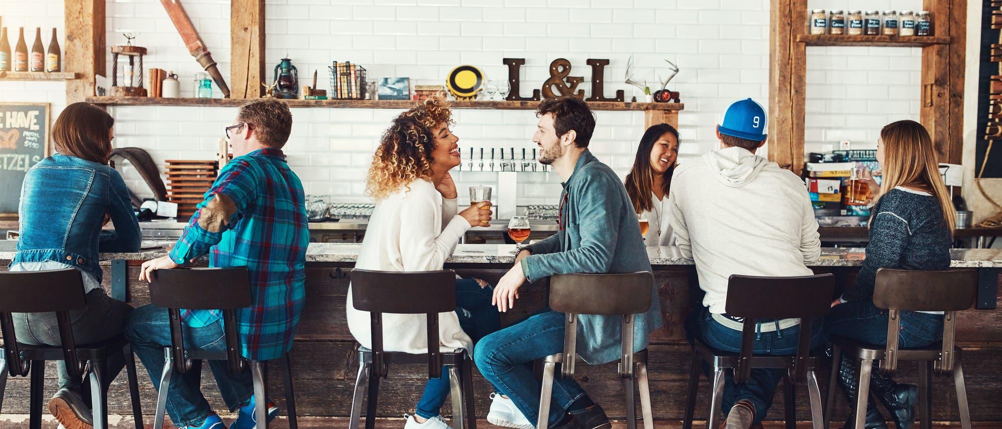 Menschen sitzen an einer Bar und unterhalten sich