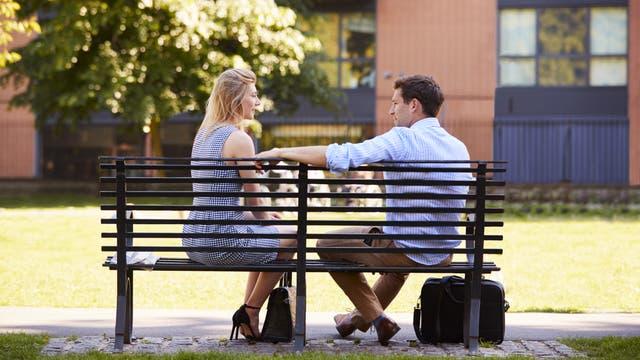Eine Frau und ein Mann sitzen auf einer Parkbank und unterhalten sich