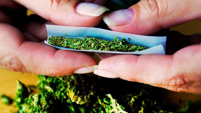 Zwei Hände drehen einen Joint