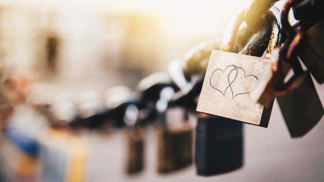 Schlösser an einer Brücke und eine Haftnotiz mit zwei Herzen