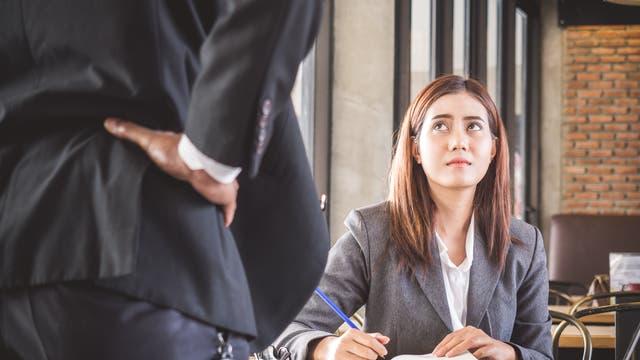 Ein Chef baut sich bedrohlich vor seiner Mitarbeiterin auf