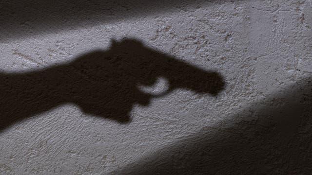 Schatten einer Pistole an der Wand