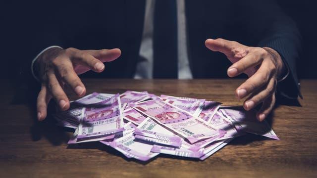 Mann streckt gierig die Hände nach Geld aus