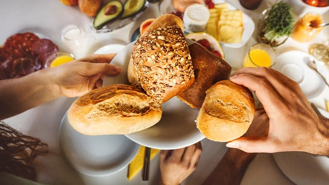 Teller mit Brot und Brötchen am Frühstückstisch