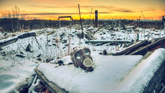 Eine Winterlandschaft mit Gasmaske im Vordergrund.