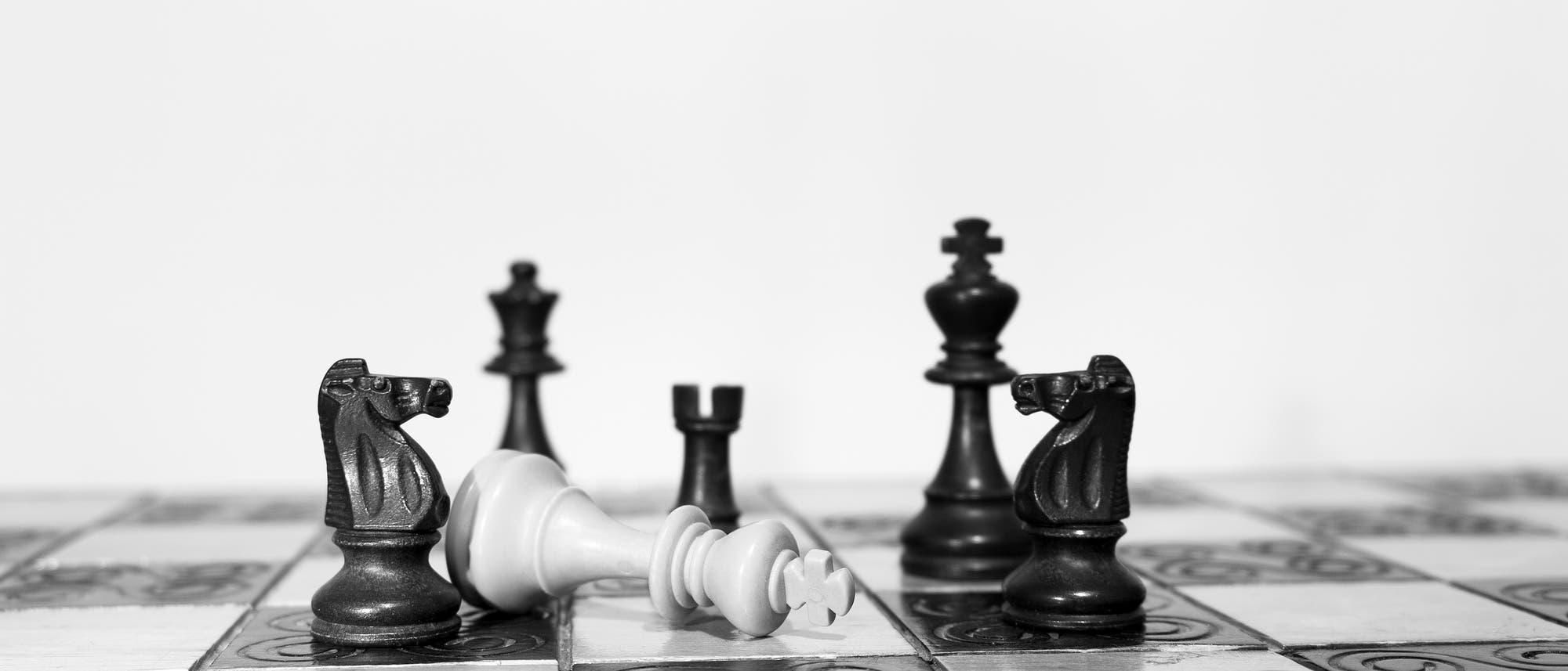 Schachfiguren auf einem Brett: Der weiße König ist gefallen