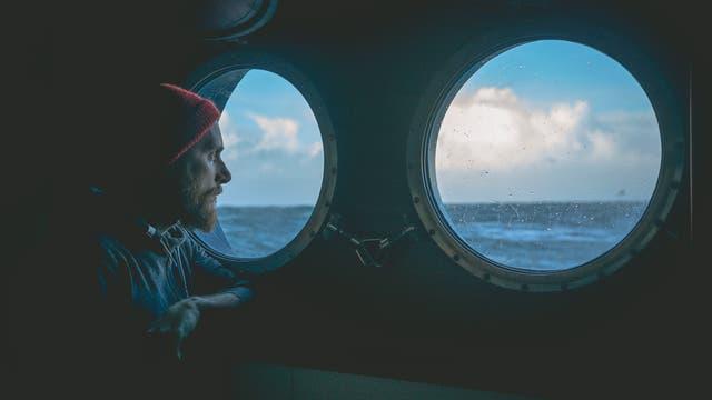 Seemann schaut aus dem Bullauge