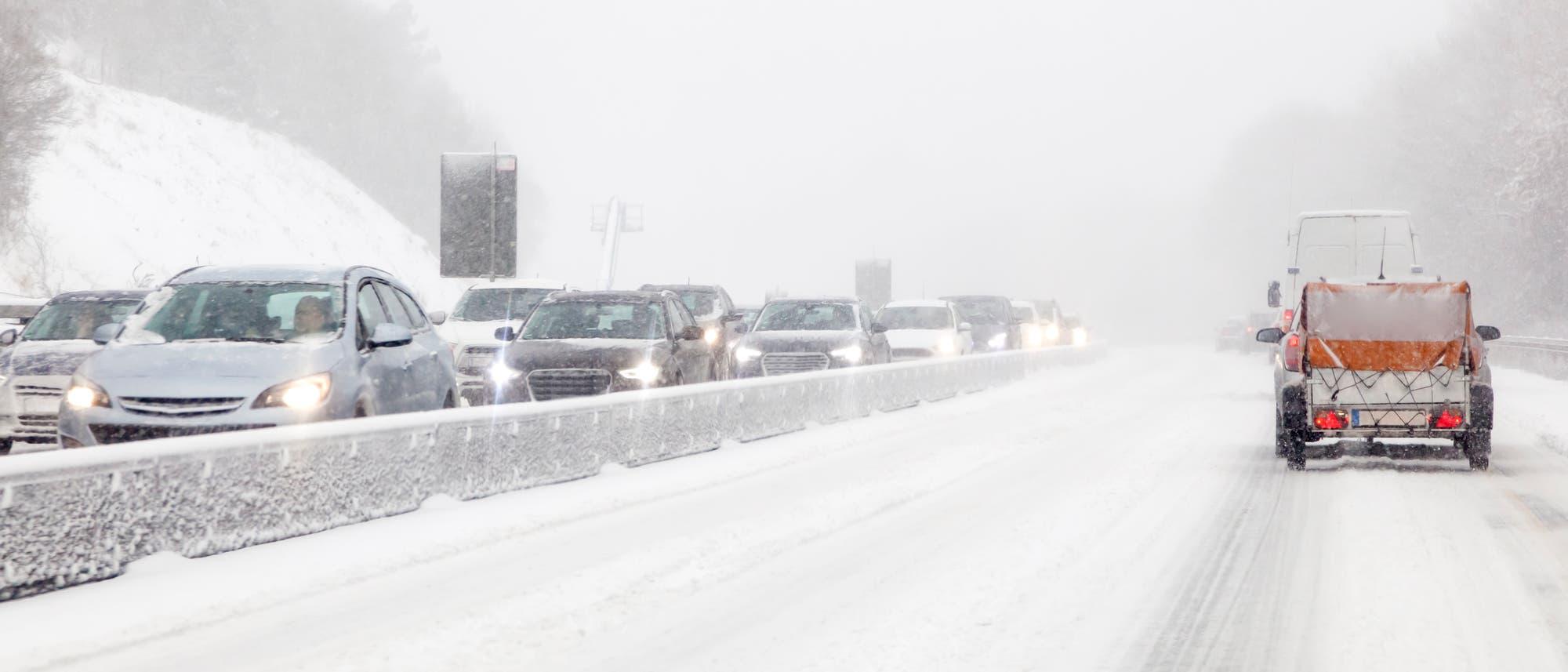 Eine Straße im Neuschnee, auf der Gegenspur stauen sich die Autos.