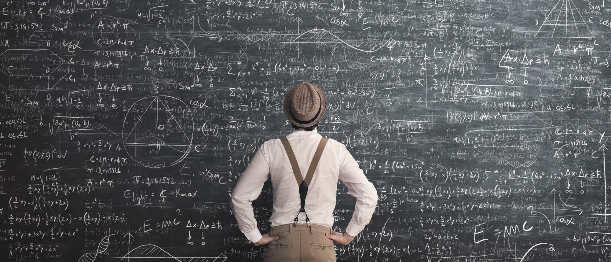 Ein Mann steht vor einer riesigen Tafel voller mathematischer Berechnungen