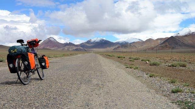Fahrrad mit viel Gepäck auf einer Schotterstraße in Tadschikistan