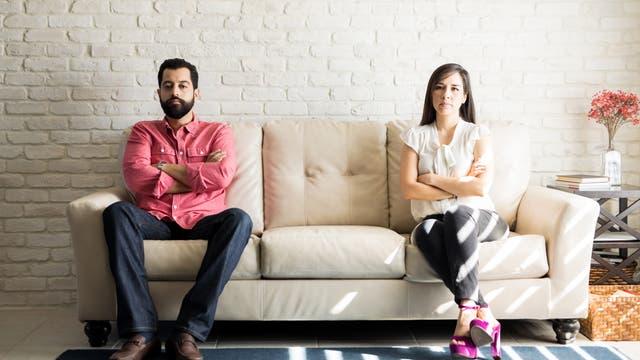 Ein Mann und eine Frau sitzen an verschiedenen Enden eines Sofas und schauen sich nicht an.