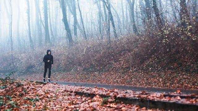 Ein Jogger in einem herbstlichen Wald bei Nieselregen.