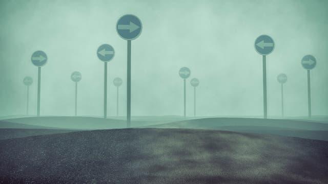 Schilder im Nebel, die in verschiedene Richtungen weisen