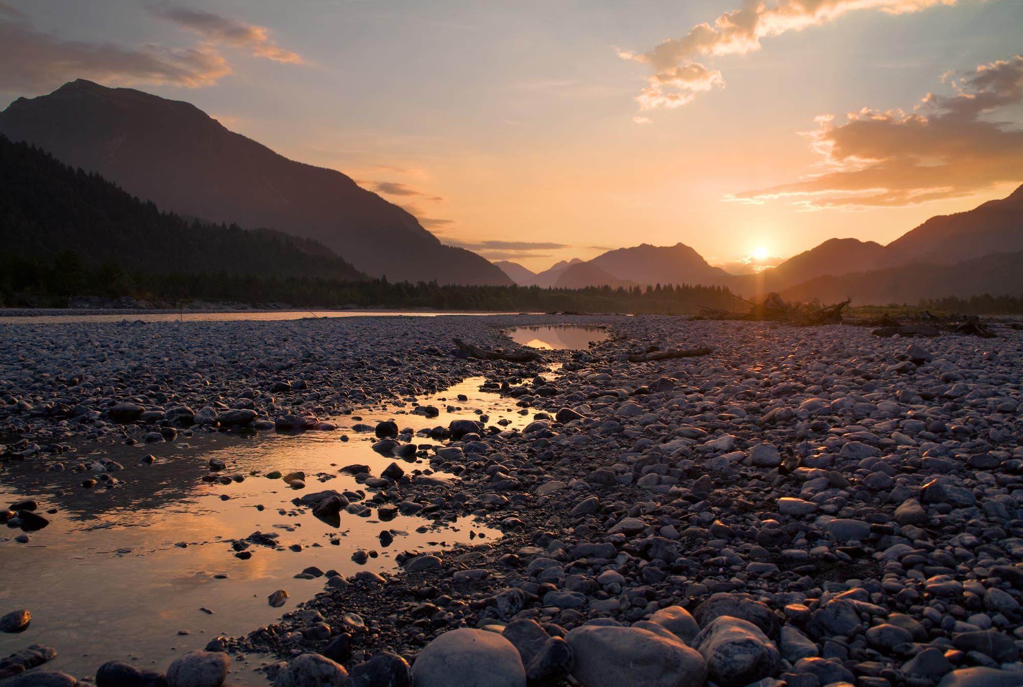 Steine im Flussbett im Gegenlicht