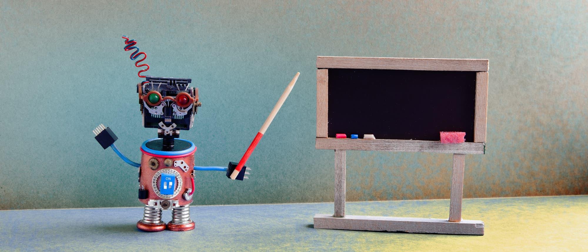 Ein kleiner Roboter steht vor einer Tafel