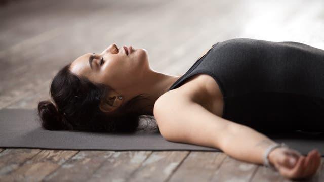 Frau meditiert im Liegen