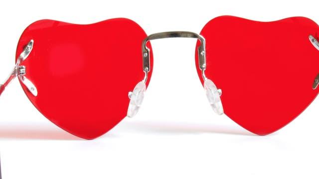 Eine Sonnenbrille mit roten Gläsern, die die Form eines Herzen haben.