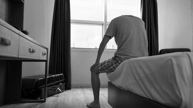 Junger Mann sitzt mit gebeugtem Körper auf dem Bett eines kahlen Raums