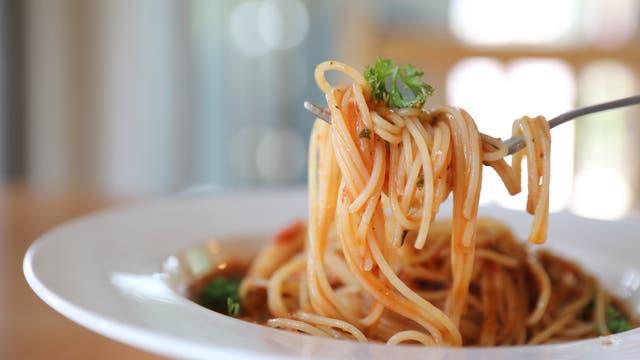 Eine mit Spaghetti umwickelte Gabel schwebt über einem sehr vollen Teller mit Spaghetti bolognese.