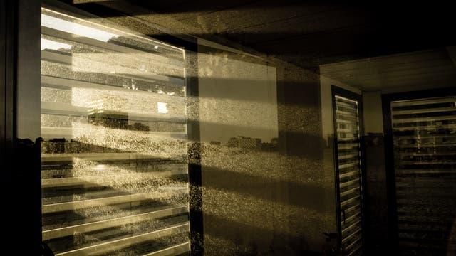 Licht fällt durch ein teilweise abgedecktes Fenster ins Innere eines Gebäudes und erzeugt ein Streifenmuster auf dem Staub des Zimmers.
