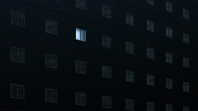 An einem Häuserblock ist nur ein einziges Fenster erleuchtet.