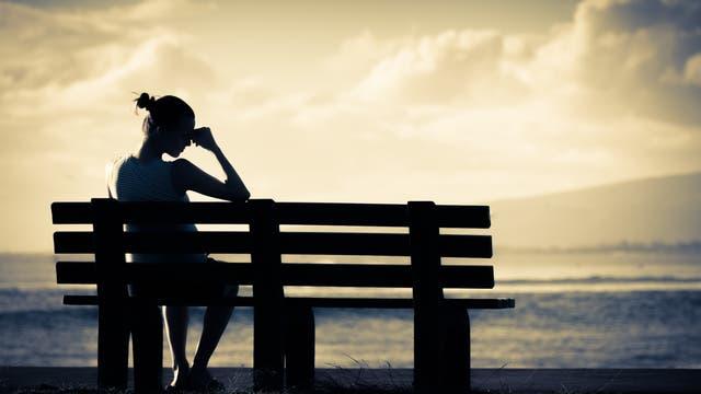 Frau sitzt im Schatten auf einer Bank