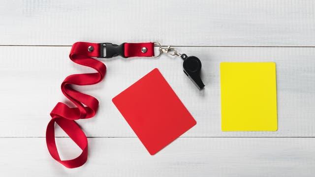 Schiedsrichterpfeife neben roter und gelber Karte