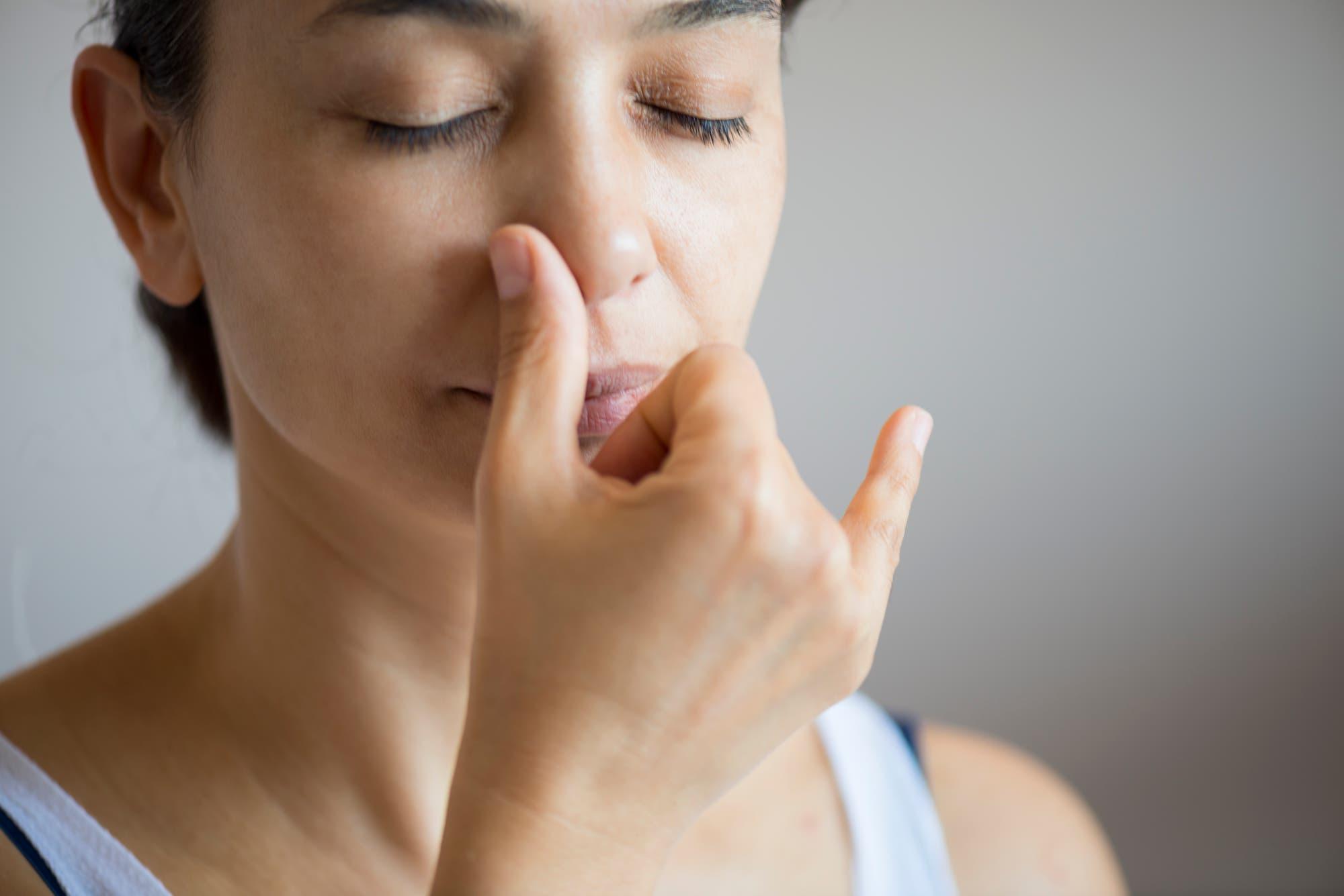 Frau demonstriert Wechselatmung durch die Nase