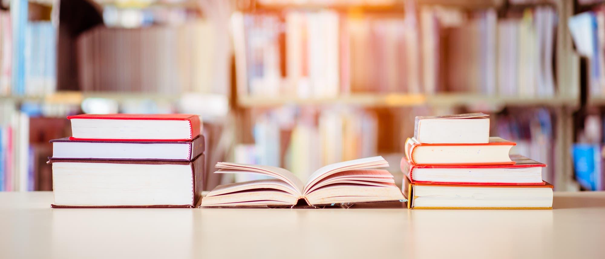 Bücherstapel vor Bücherregal in einer Bibliothek.