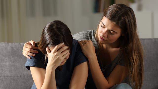 Mädchen legt tröstend den Arm um ein anderes Mädchen