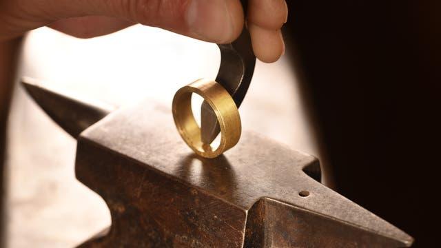 Auf einem sehr kleinen Amboss prägt ein Juwelier mit einem Schlageisen sein Logo in die Innenseite eines breiten und etwas geschmacklosen Goldringes.