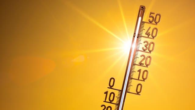Ein Thermometer vor der Sonne in einem orangefarbenen Himmel zeigt 35 Grad.