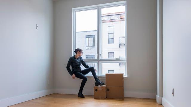 Mädchen sitzt mit ein paar Kisten am Fenster eines leeren Zimmers