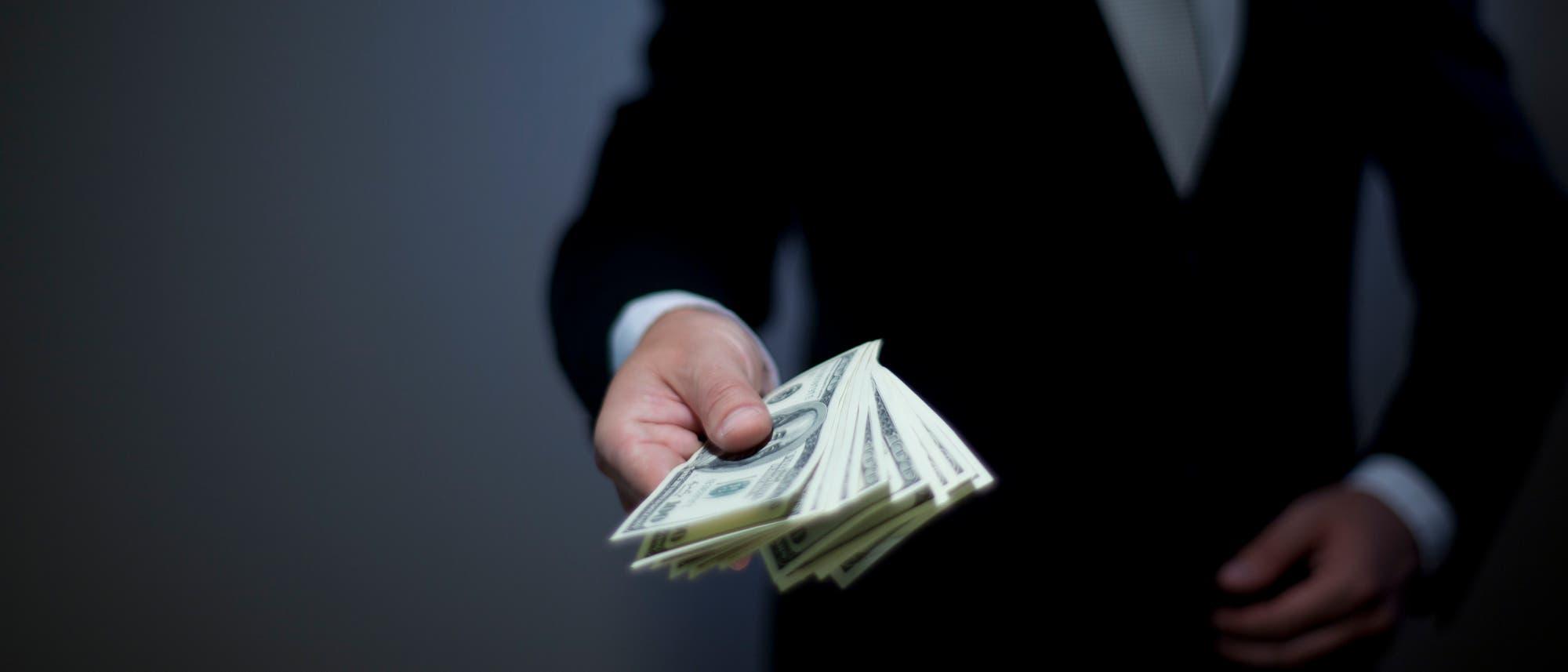 Eine Hand bietet dem Betrachter einen Stapel Geldscheine an