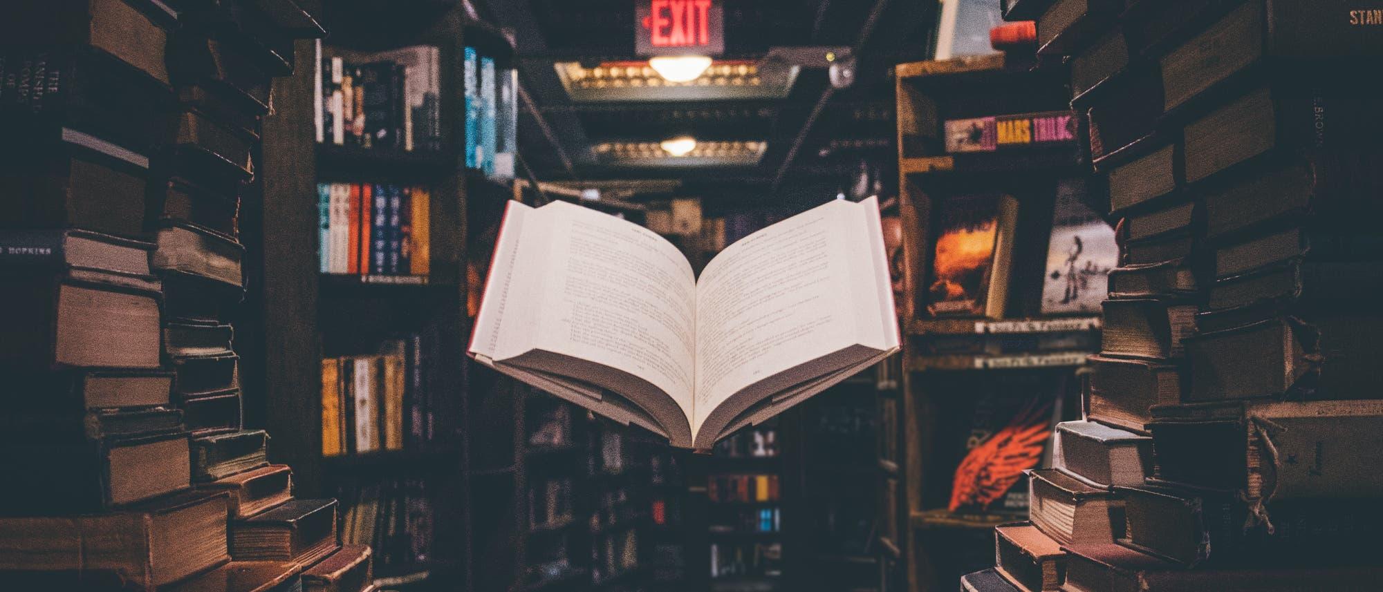 Schwebendes offenes Buch in einem Bücherfenster einer Bibliothek