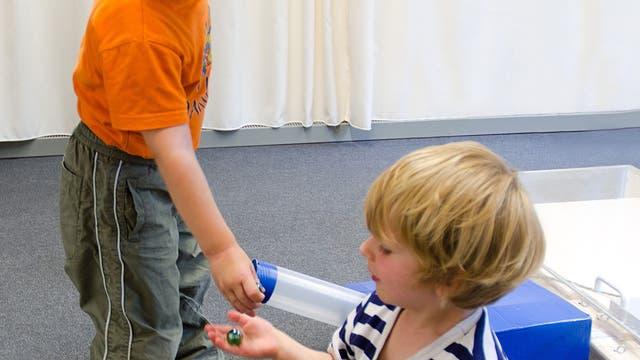 Kinder teilen Murmeln nach Zusammenarbeit