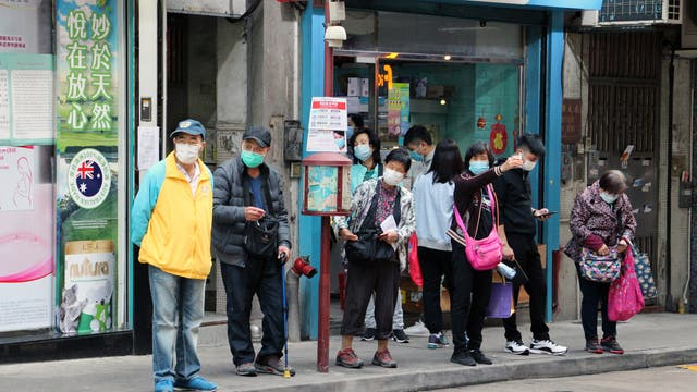 Ältere Menschen warten mit Masken an einer Bushaltestelle in Macau, China, in der Nähe des öffentlichen Krankenhauses.
