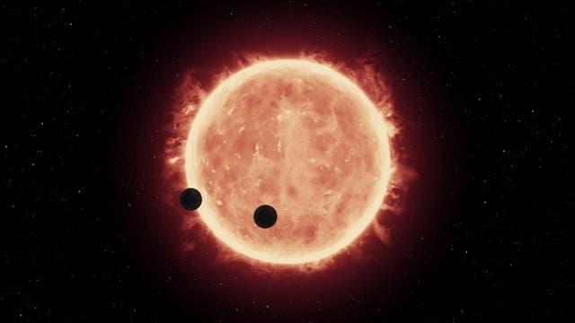 Künstlerische Darstellung von zwei Planeten von TRAPPIST-1 im Durchgang vor ihrem Stern