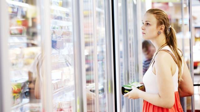 Eine Frau sieht in ein Kühlregal.