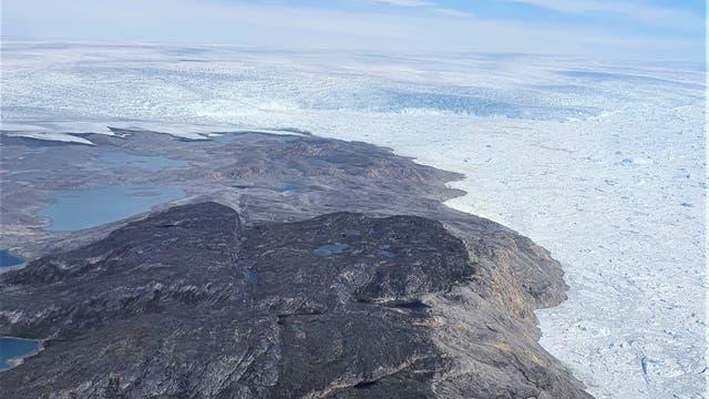 Die Front des Gletschers Jakobshavn Isbræ im Hintergrund mündet in den Kangia-Fjord. Die auf den Bergen hinterlassenen Spuren zeugen von der Gletscherposition um 1875.
