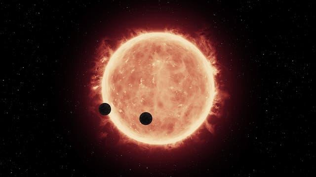 Künstlerische Darstellung eines roten Zwergsterns mit zwei Planeten