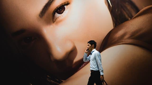 Asiate vor Werbeplakat mit Frauengesicht