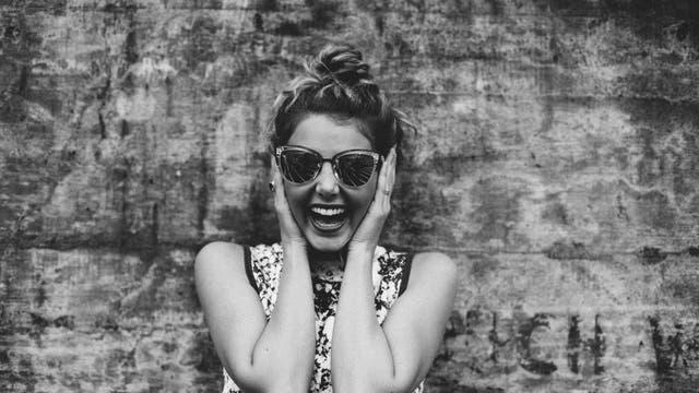 Frau freut sich und greift sich ungläubig an die Ohren