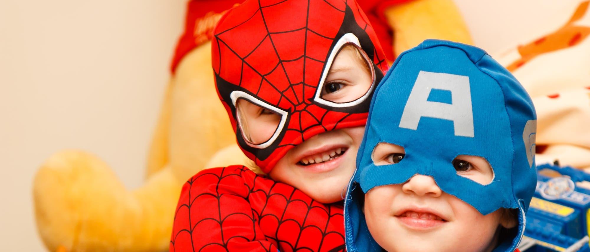 Kinder in Spiderman und Captain America Kostümen