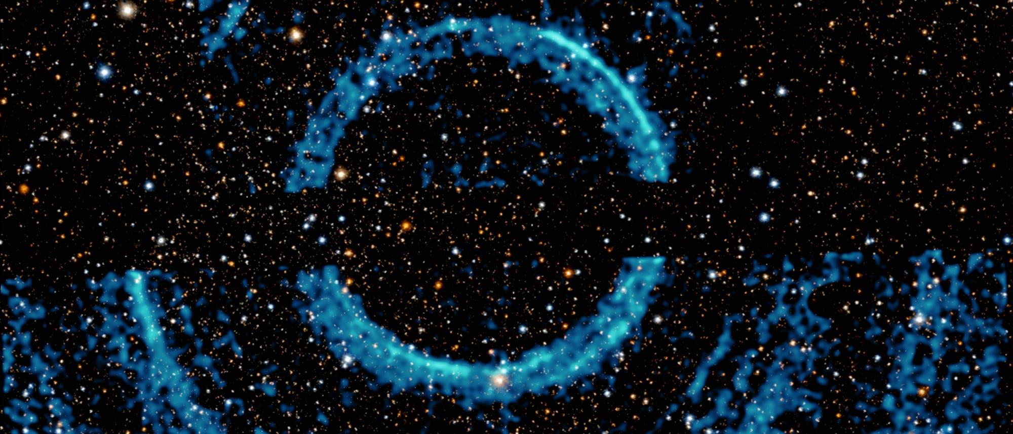 Röntgenechos um V404 Cygni, dargestellt als blaue Ringe auf einer Abbildung des Sternenhimmels im sichtbaren Licht.