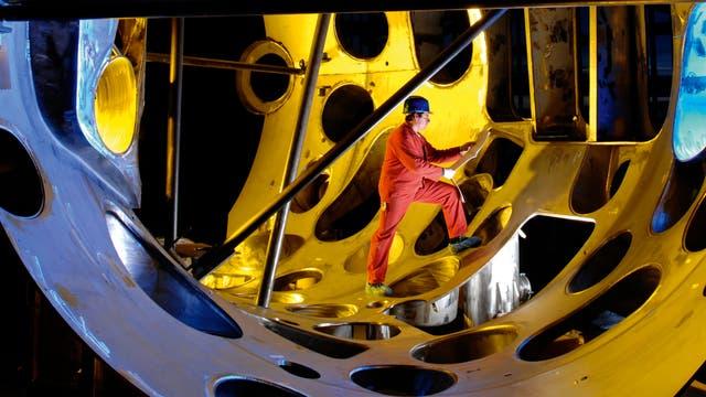 Ein Techniker arbeitet an einem Modul des Außengefäßes von Wendelstein 7-X