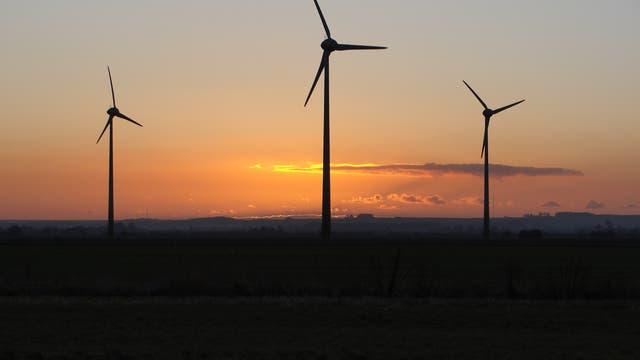 Drei Windräder in der Abenddämmerung