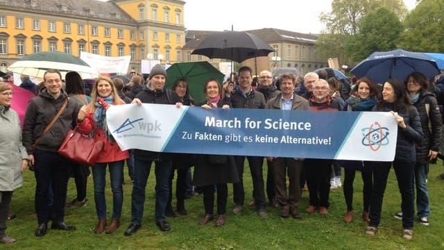 Wissenschaftsjournalisten präsentieren das Banner des Science March vor dem Gebäude der Uni Bonn.